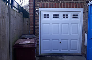 A Garador Beaumont with windows steel up and over garage door. With a white timber frame and white PVC cladding. Door fitted near Reading, Berkshire.