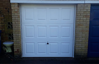A Garador Georgian style up and over steel garage door with a white steel frame. Fitted in Sandhurst. Berkshire.