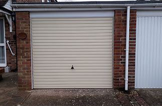 A Garador steel range up and over garage door in the Horizon style in Light Ivory with a white steel frame. Fitted in Bagshot, Surrey.