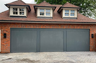 Three bespoke Woodrite Accoya timber up and over garage doors. With Matching cladding. Fitted in Jordans, Buckingham.