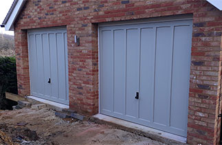 Two Woodriet Somerset range Churchill style up and over garage doors. In a Farrow and Ball colour match with white steel frames. Fitted near Farnham. Surrey.