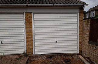 A Garador steel range up and over garage door. From the Guardian Range in the Horizon style. With a white steel frame. Fitted in Farnborough. Hampshire.