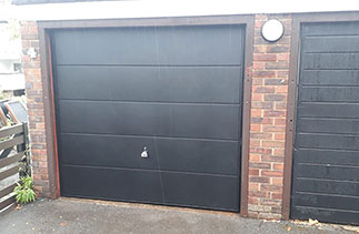 A Garador steel range up and over garage door in the Ascot Style. In Black with a black steel frame. Fitted behind the existing timber frame. Fitted in Weybridge. In Surrey.