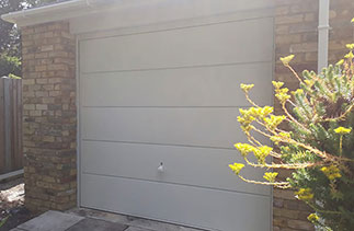 A Garador steel range up and over garage door in the Ascot Style. In White with a White steel frame and a White handle. Fitted in Camberley. Surrey.
