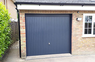 A Garador steel range up and over garage door in the Carlton style. In Anthracite Grey with a Anthracite Grey steel frame and a Chrome effect handle. Fitted in Camberley. Surrey.