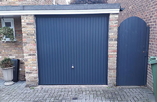 A Garador steel range up and over garage door in the Carlton style. In Anthracite Grey with a matching steel frame and a Chrome effect handle. Fitted in Windlesham. Surrey.