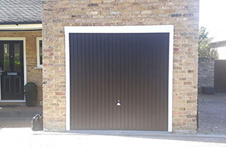 A Garador steel range up and over garage door in the Carlton style. In Black with a White steel frame. With a Chrome effect handle. Fitted in Camberley. Surrey.