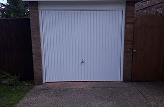 A Garador steel range up and over garage door in the Carlton style. In White with a White steel frame and a Chrome effect handle. Fitted in Yatley. Hampshire.