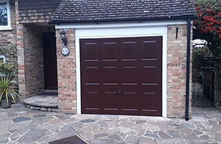 A Garador steel range up and over garage door in the Georgian style. In Burgundy Brown with a white steel frame. Fitted in Camberley. Surrey.