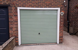A Garador steel range up and over garage door in the Horizon style. In Chartwell Green with a White steel frame and White pvc on the existing timber frame. Fitted near Aldershot. Hampshire.