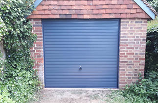 A Garador steel range up and over garage door in the Horizon style. In Slate Grey with matching steel frame. Fitted in Godalming. Surrey.