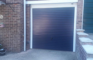 A Garador steel range up and over garage door in the Horizon style. In steel Blue colour with a White steel frame. Fitted in Sandhurst. Berkshire.