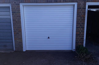 A Garador steel range up and over garage door in the Horizon style. In White with a White steel frame and With White pvc to cover the existing timber frame. Fitted in Guildford. Surrey.