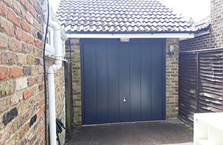 A Garador steel range up and over garage door. In the Windsor style. In Anthracite Grey with a matching steel frame and a Chrome effect handle. Fitted in Lightwater. Surrey.