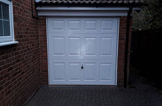 A Garador steel range up and over garage in the Beaumont style. In White with a White steel frame. Fitted in Windlesham. Surrey.