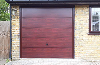 A Garador steel range up and over garage in the Wentwood  design. In Rosewood with a Burgundy Brown steel frame and with Rosewood pvc. Fitted in Camberley. Surrey.