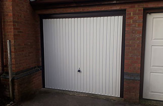 A Garador steel up and over garage door in the Carlton style in White. With a Burgundy Brown steel frame with Rosewood pvc. Fitted in Guildford. Surrey.