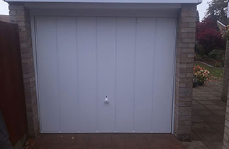 A Garador steel up and over garage door in the Windsor style. With a white steel frame. Fitted in Frimley. Surrey.