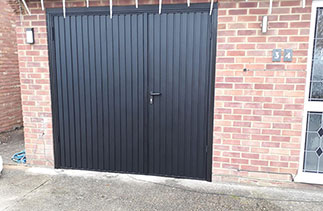 A set of Garador steel side hinged garage doors. In a 2/3rd x 1/3rd split. In Black with a Black steel frame. Fitted in Mytchet. Surrey