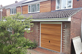A Woodrite timber up and over garage door in the Buckingham range. In the Hardwick style. Finished in a Base coat light oak stain. With a white steel frame. Fitted in Winchester. Hampshire.