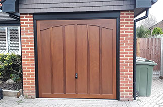 A Woodrite up and over timber garage door from the Somerset range in the Wasford style. Finished in Light Oak on a Dark board. With a Black steel frame and Black Ash pvc. Fitted in East Horsley. Surrey.