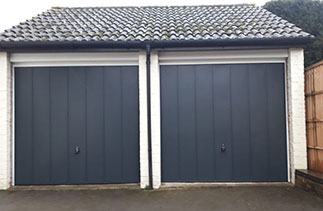 Two Garador steel range up and over Garage Doors in the Windsor style. In Anthracite Grey with White steel frames. Fitted in Guildford. Surrey.
