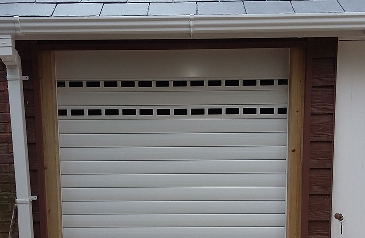 A Gliderol manual insulated roller shutter garage door fitted to a bin store with punched and unglazed slats for ventilation