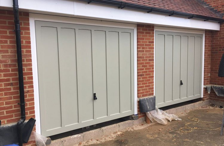 Two Churchill style timber garage doors  in colour match Farrow and Ball French Grey with White steel frames