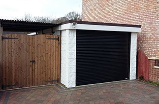 A Black Gliderol compact insulated roller shutter garage door fitted in Ashvale, Surrey.