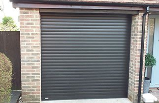 A Black Wood grain Seceuroglide Excel insulated roller shutter garage door supplied with white internal slats. Fitted in Bagshot, Surrey.