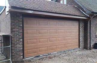 A Carteck Georgian sectional garage door in Winchester Oak with a Brown steel frame fitted between the opening. Fitted in Chobham, Surrey.