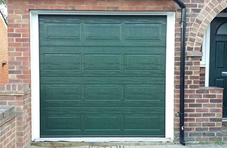A Carteck Georgian sectional garage door in Fir green. Fitted within the brick work but behind the lintel, complete with a white steel frame and white UPVC as required.