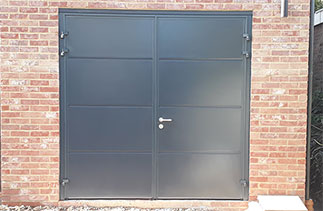 A set of Carteck insulated Solid rib side hinged garage doors in Anthracite Grey (Smooth finish) with No branding badge and stainless steel handle and lock cover. Fitted in Surbiton, Surrey.