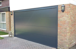 A Carteck solid ribbed style sectional garage door in Anthracite with a Anthracite painted frame and Anthracite UPVC. This door and frame was fitted between the brick opening to cover the old mastic lines and untidy brick work and to avoid having to clad the inside brick faces with large slabs of UPVC. By fitting it this way it also covered the garage floor which would have been visible if the frame was fitted behind the opening. Door fitted in Ascot, Berkshire.