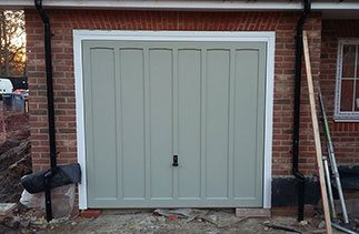 A Woodrite timber up and over garage door  finished in a colour match to Farrow and Ball French Grey with a white steel frame and chassis.