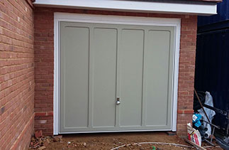 A Garador Grantham timber up and over garage door in a colour match to Farrow and Ball French Grey. Fitted with a white steel frame on retractable plus door gear with a Chrome effect handle. Fitted in Farnham, Surrey