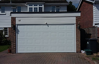 A Garador Georgian Premium Sectional Garage Door with NO branding badge with matching side cover profiles and fitted with a electronic operator. Fitted in Hartney Winteny, Hampshire.