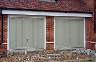Two timber Churchill style garage doors in a colour match to Farrow & Ball French Grey. Fitted with white steel frames and white chassis to plot 5 in Hartley Wintney, Hampshire.