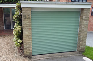 A Gliderol insulated, electronically operated Roller shutter Garage Door in Chartwell Green with white guides and a white 90 degree half top box. Fitted in Camberley, Surrey.