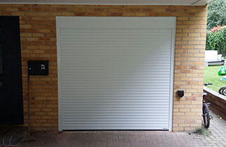 A Gliderol White 55 compact insulated roller shutter garage door fitted within the opening. Fitted in Blackwater, Surrey.