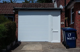 A Gliderol White insulated, electronically operated compact roller shutter garage door with a full internal box. Complete with a UPVC cladded timber divide and a White UPVC side door. Fitted in Haslemere, Surrey.