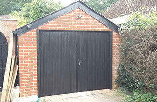 A set of Grp Black wood grain side hinged garage doors fitted with two Black timber posts. Fitted in Mytchett, Surrey.