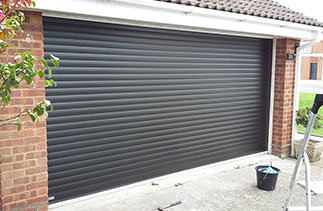 A Seceuroglide Excel roller shutter garage door in Black wood grain. This door is supplied on white slats so from inside the back face of the door is white. Fitted in Berkshire.