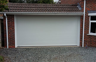"A Sws Seceuroglide Excel roller shutter garage door  with White UPVC on the inside brick faces. Fitted in Basingstoke, Hampshire. ""We are very happy with the door and the service you provided, had great fun last night making the door go up & down. We will have no hesitation in recommending you."" Maggie and Des"