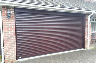 A Sws Seceuroglide Excel insulated, electronically operated Roller Shutter Garage Door in Mahogany with matching UPVC to cover the existing timber frame. Fitted in Camberley, Surrey.