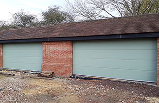 Two Carteck GSW 40-L Solid ribbed sectional garage doors in Chartwell Green Wood Grain finish. Fitted in Bramley, Nr Guildford, Surrey.
