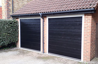 Two Carteck Centre Ribbed Black wood grain sectional garage doors with White steel frames fitted in Warfield, Berkshire. Simply a great end to end customer service experience, just like it should be. Mr A Burns.