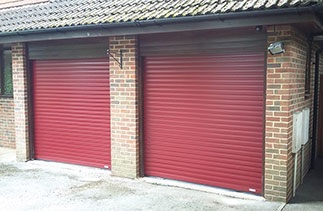 Two Gliderol Purple/Red 77mm insulated, electronically operated roller shutter garage doors. These doors were fitted so the guides and full internal boxes sit behind the existing timber frames giving full drive through width and height. Fitted in Camberley, Surrey. Hi Ben, really super pleased with the doors. A great decision in the end. Thank you and your team for the excellent customer service. Best regards, Cameron