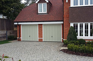 Two timber Churchill style up and over garage doors fully finished in a colour match to Farrow & Ball French Grey. Fitted in Hartley Wintney, Hampshire.