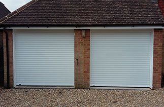 Two White Seceuroglide Excel roller shutter garage doors fitted with white upvc fascia's and white upvc on the brick faces. Fitted in Westend, Surrey.